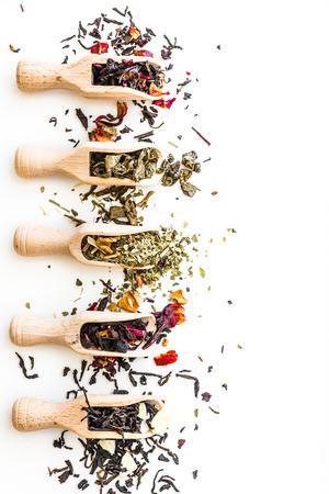 Různé sušeného čaje v dřevěných naběračky na bílém stole