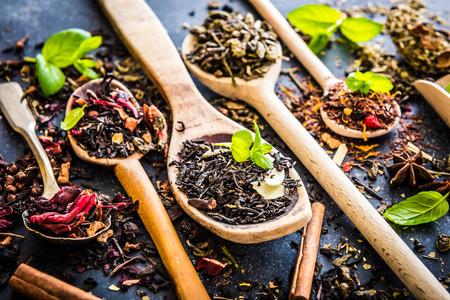Tipi Virious di tè in cucchiai di legno sul tavolo nero Archivio Fotografico - 38484820