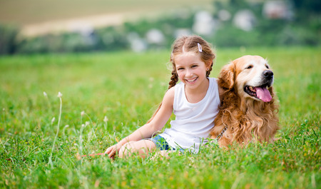 Smiling Little girl sitting on the grass with golden labrador