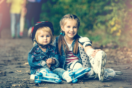 rollerblade: two beautiful sisters on roller skates in park Stock Photo