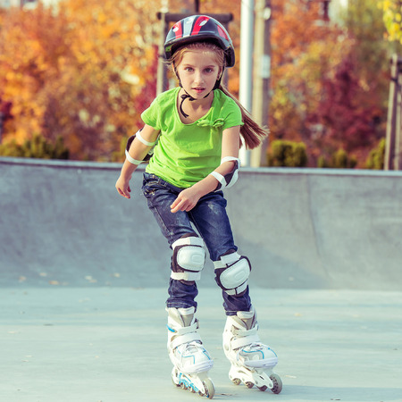 skating fun: Little girl on roller skates in helmet at a park
