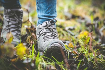 los pies en los zapatos de un camino forestal Foto de archivo