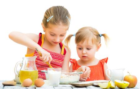niños cocinando: dos hermanitas cocinar aislados en un fondo blanco