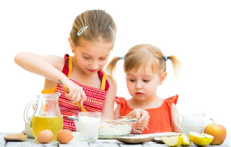 two little sisters cooking isolated on a white background Standard-Bild