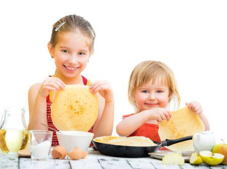 funny sisters cooking pancakes on kitchen, white background photo