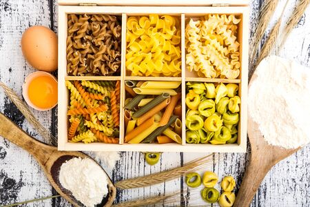 six types of pasta, tortellini and other products on textured wooden table photo