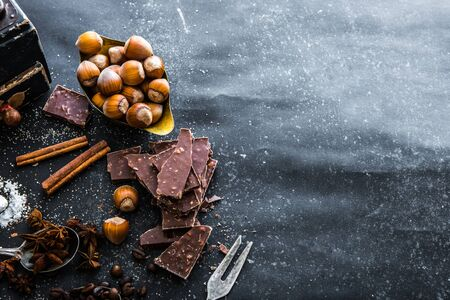 chocolate background: Sweet spices in the spoons and chocolate on a table black