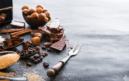 Chocolate, nuts, spices in the spoons on the table dark Stockfoto