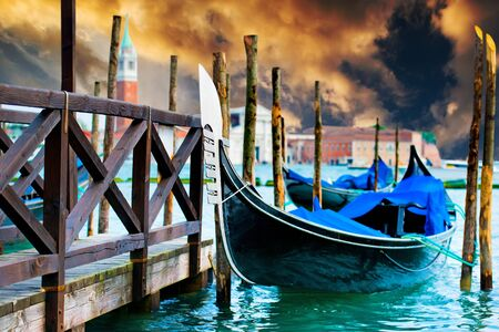 gondola: Gondola on the Grand Canal pier in Venice at sunset Stock Photo
