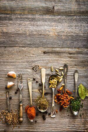 especias: condimentos y especias en las cucharas en una tabla de madera marrón Foto de archivo