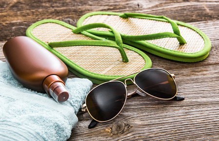Beach accessories. Summer shoes and towel with sunglasses and suntan lotion on a wooden background