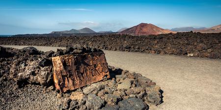 los hervideros: beautiful desert landscape with a metal sign Los Hervideros on Lanzarote island , Canary Islands