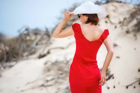 yellow dress: beautiful young woman in evening red dress and white hat on a background of a sand desert