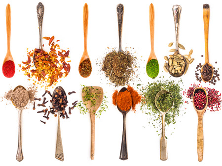 photo collage of metal and wooden spoons with spices on a white background