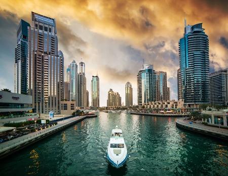 Dubai, Emiratos Árabes Unidos - 14 de diciembre 2013: Rascacielos modernos y canal de agua con los barcos de Dubai Marina al atardecer, Emiratos Árabes Unidos