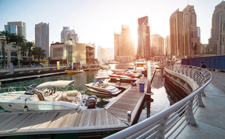 urban landscapes: Panoramic view with modern skyscrapers and water pier of Dubai Marina at sunset, United Arab Emirates