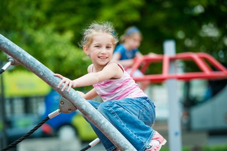 cute beautiful smiling little girl on a playground Standard-Bild