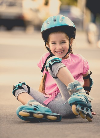 kids wear: beautiful girl on the rollers in helmet and protection
