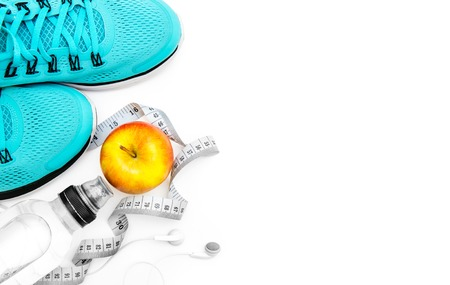 water shoes: sport background: blue running shoes  and apple with objects isolated on white background