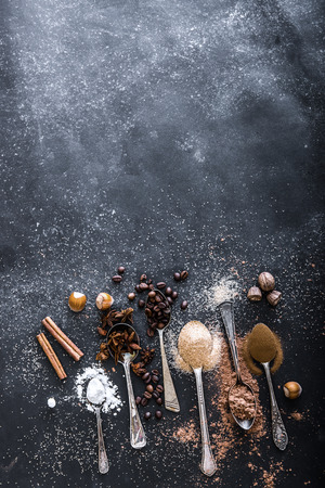 Sweet spices in the spoons on the table a black background photo