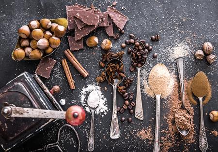 ESPECIAS: Especias dulces en las cucharas y chocolate en la mesa de un negro Foto de archivo
