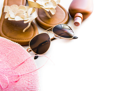 Beach accessories. Summer shoes and hat with sunglasses and suntan lotion on a white background Standard-Bild