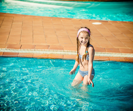 little happy girl swims in the pool Stock Photo