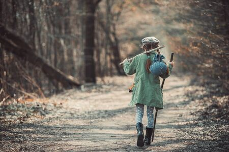 'young things': little girl goes on a footpath in the forest with stuff, photo in retro style Stock Photo