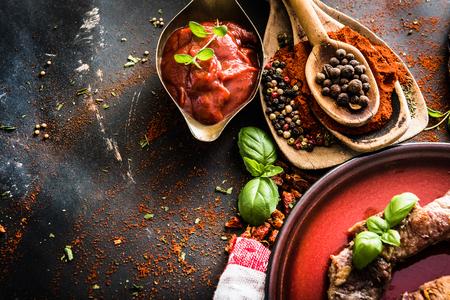carne roja: carne a la parrilla en un plato con salsa de tomate, especias sobre fondo negro con textura