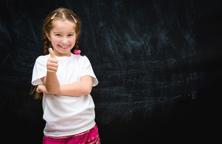 school board: cute happy little girl with thumbs up on the background of the school board Stock Photo
