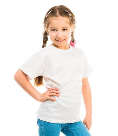 niño modelo: niña linda en una camiseta blanca y pantalones vaqueros azules sobre un fondo blanco