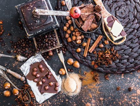 chocolate, cocoa and various spices on black table
