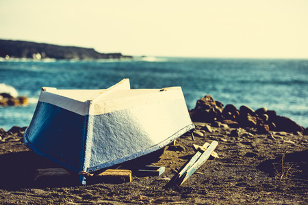upturned: upturned boat on a sandy shore on sea background Stock Photo
