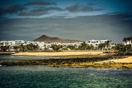 township: desert Lanzarote coast with a township on the background, Canary Islands, Spain