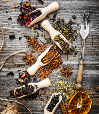odorous: odorous dry teas in scoops on wooden background Stock Photo