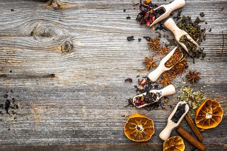 odorous dry teas in scoops on wooden background Foto de archivo
