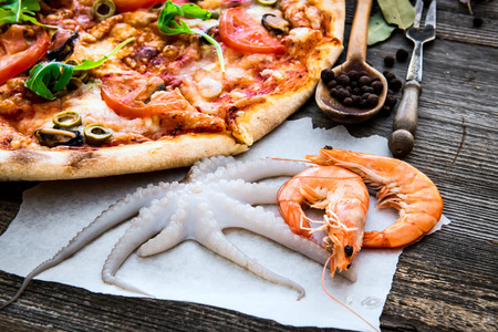 pizza pie: Tasty pizza with seafood on a wooden table Stock Photo