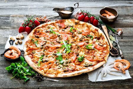 seafood: Big tasty pizza with seafood, tomatoes on a wooden table Stock Photo