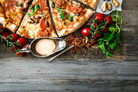 italienisches essen: Leckere Meeresfrüchte Pizza mit Kirschen auf einem Holztisch