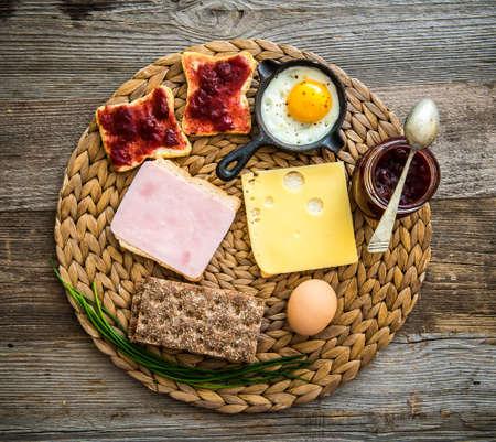 jamon y queso: Desayuno Inglés con queso, jamón, pan blanco y gris y mermelada en el fondo de madera