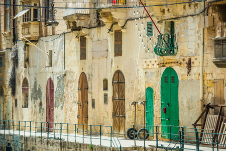 view of a wooden doorway: street with colorful gates in Vallatta historical center in Malta
