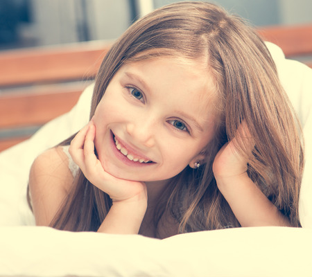 cute girl: cute little girl lying in a bad under a blanket and smiling Stock Photo