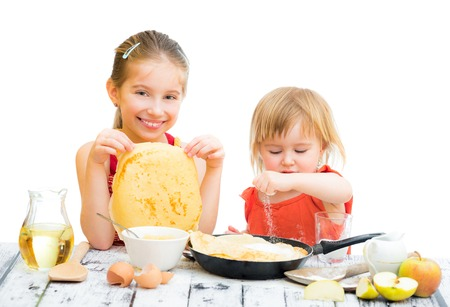 funny sisters cooking pancakes on kitchen, white background