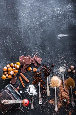Spezie dolci in cucchiai e cioccolato su un tavolo nero Archivio Fotografico - 43020949