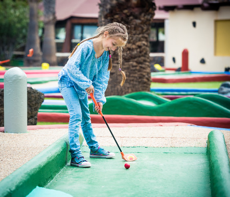 Cute little girl playing golf