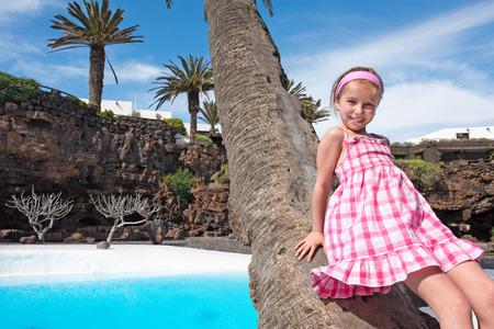 leaned: girl leaned against a palm tree near beautiful pool zone Stock Photo