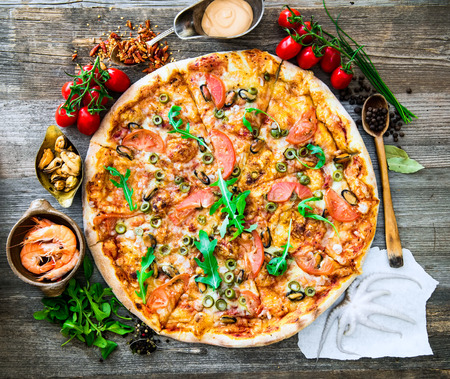 delicious pizza with seafood on wooden table Imagens