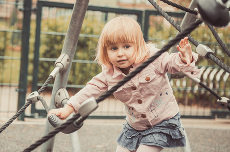 wondered: wondered little girl on a playground Stock Photo