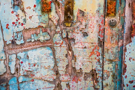 door handle: texture of old wooden door with crumbling paint layers Stock Photo