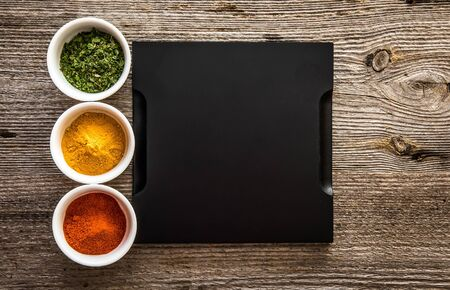 both sides: black tray with different spices in bowls on both sides